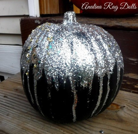 adding glitter to a pumpkin for halloween